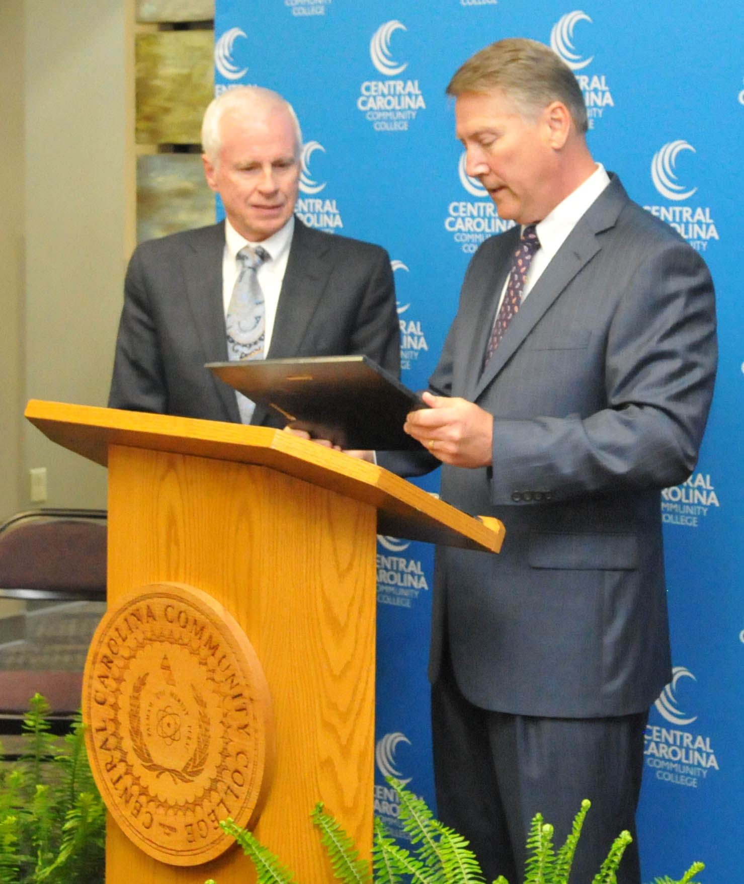 "Click to enlarge,  Wayne Staton (left) receives the plaque honoring the naming of the Central Carolina Community College William W. and Ellen B. Staton Department of Paralegal Studies from former North Carolina Lt. Gov. Dennis Wicker (right), a friend of the Staton family who once served with William W. ""Bill"" Staton in the North Carolina General Assembly."