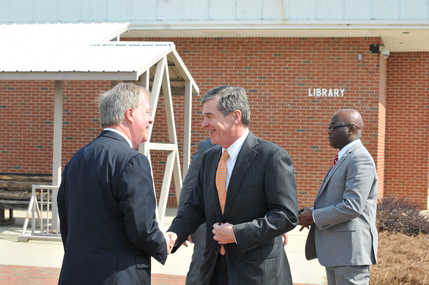 Click to enlarge,  Central Carolina Community College President Dr. T. Eston Marchant (left) greets North Carolina Gov. Roy Cooper upon his arrival to the CCCC Lee Main Campus on Wednesday, April 12.