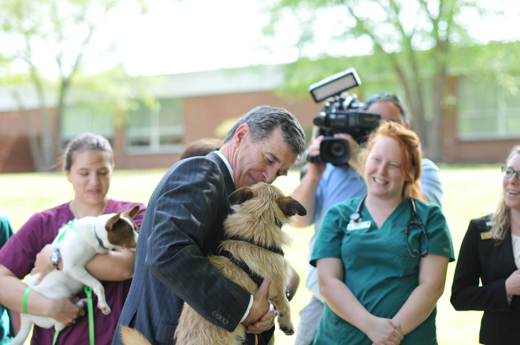 Click to enlarge,  North Carolina Gov. Roy Cooper holds a dog from Central Carolina Community College's Veterinary Medical Technology program on Wednesday, April 12, at the CCCC Lee Main Campus.