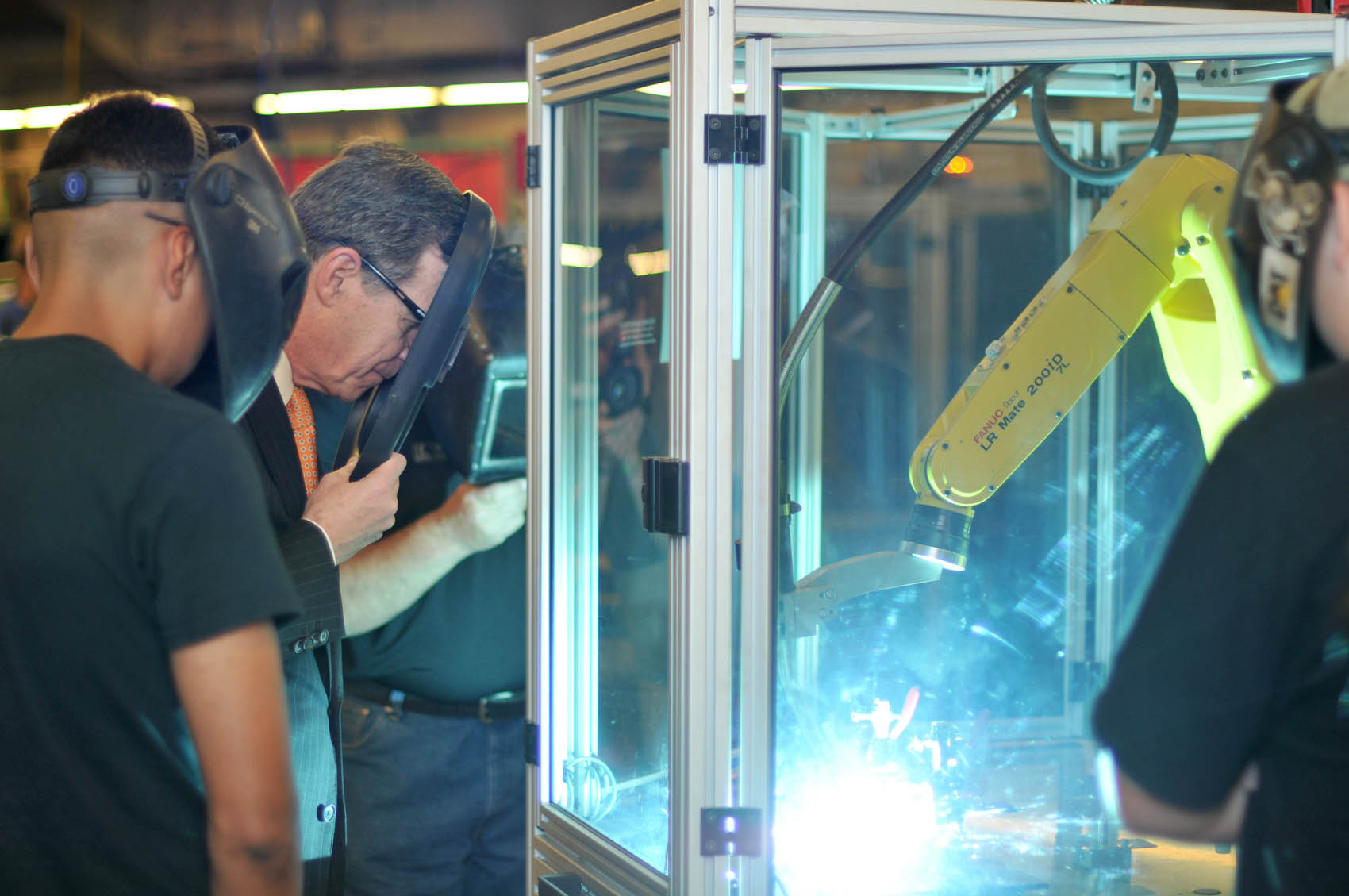 Click to enlarge,  North Carolina Gov. Roy Cooper (holding shield) gets an up-close view of a robotic welding demonstration on Wednesday, April 12, at the Central Carolina Community College Lee Main Campus.
