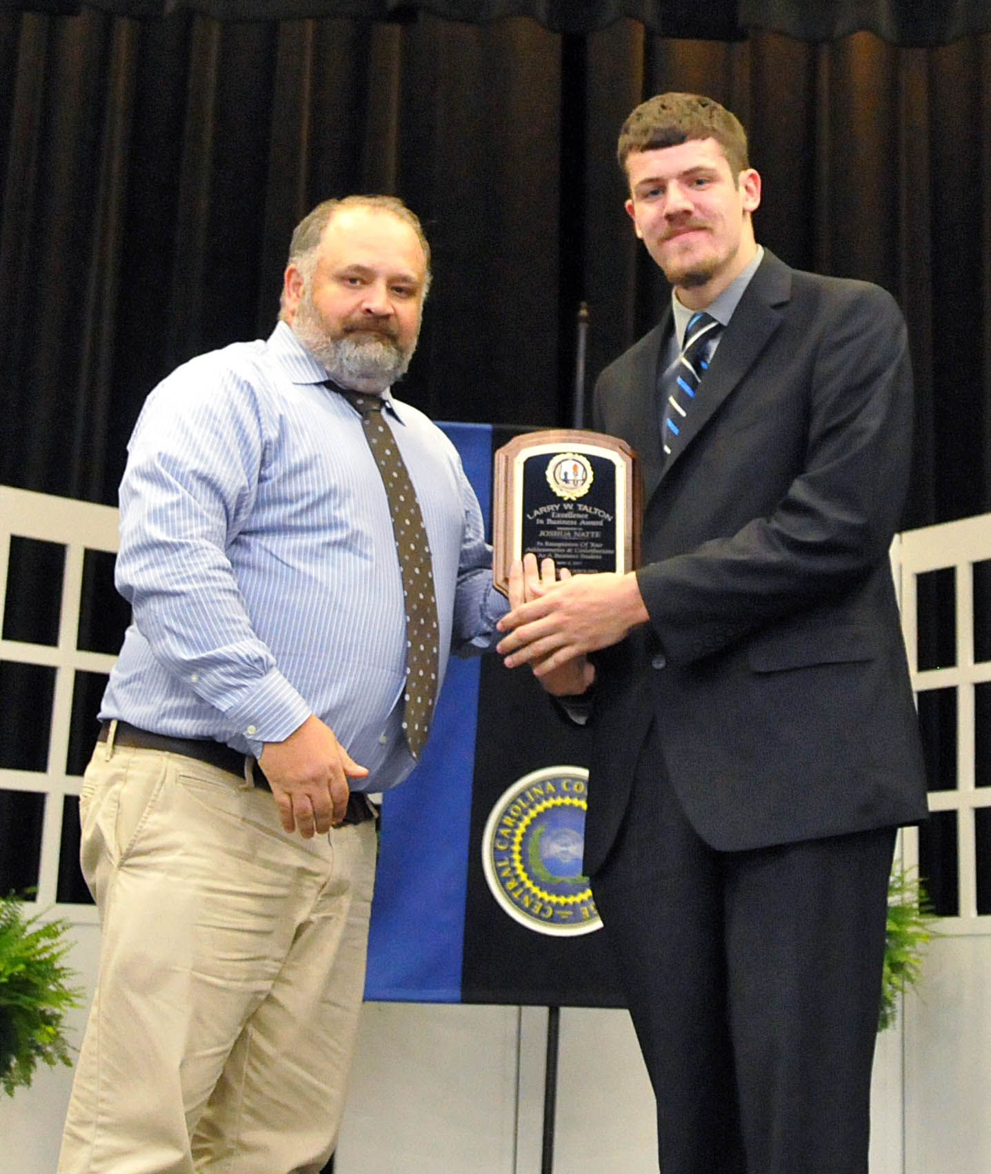 Click to enlarge,  Joshua Natte (right) is recipient of Central Carolina Community College's Larry Talton Excellence in Business Award. Presenting the award to Natte is Michael Fann, CCCC Business Technologies - Lead Instructor.