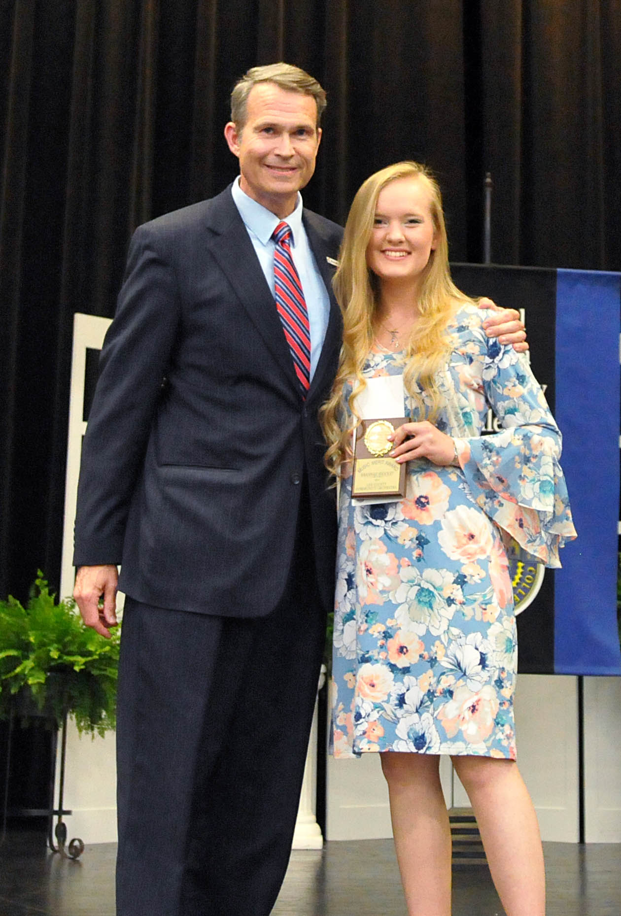 Click to enlarge,  Savannah Shockey (right) is recipient of Central Carolina Community College's Lee County Orchestra Achievement Award. Presenting the award to Shockey is Ken Hoyle, CCCC Vice President of Student Services.