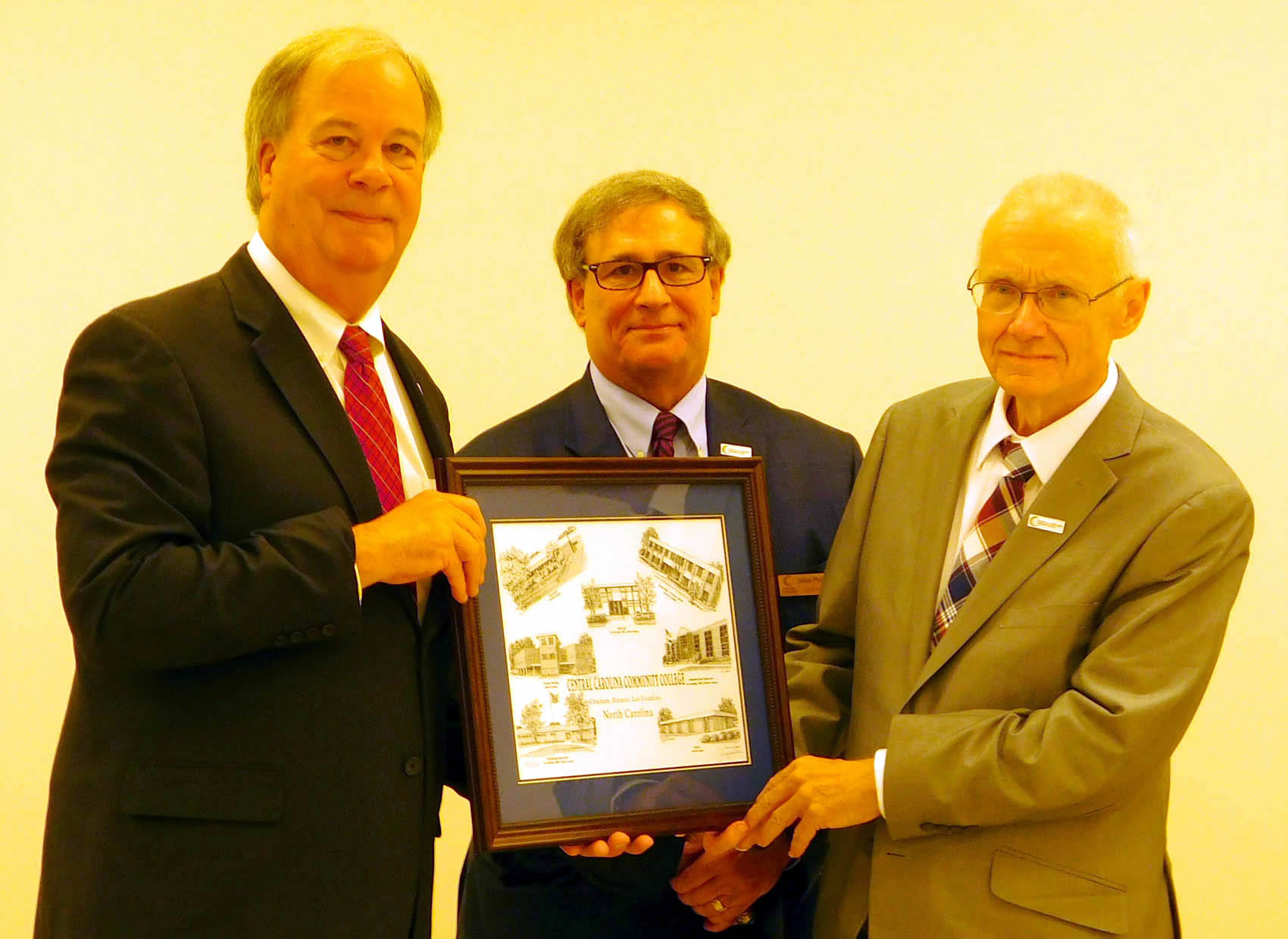 Click to enlarge,  Keith Clark (right), pictured with CCCC President T. Eston Marchant (left) and CCCC Board of Trustees Chairman Julian Philpott (right), was presented with a Jerry Miller print of CCCC buildings, as he was honored for his service as a CCCC Trustee on Wednesday, Aug. 9.