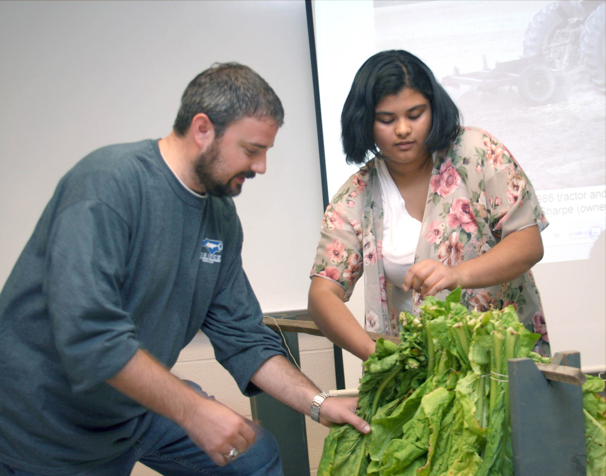 Click to enlarge,  Patrick Kelly (left) shows Central Carolina Community College student Paula Funes how to loop tobacco.