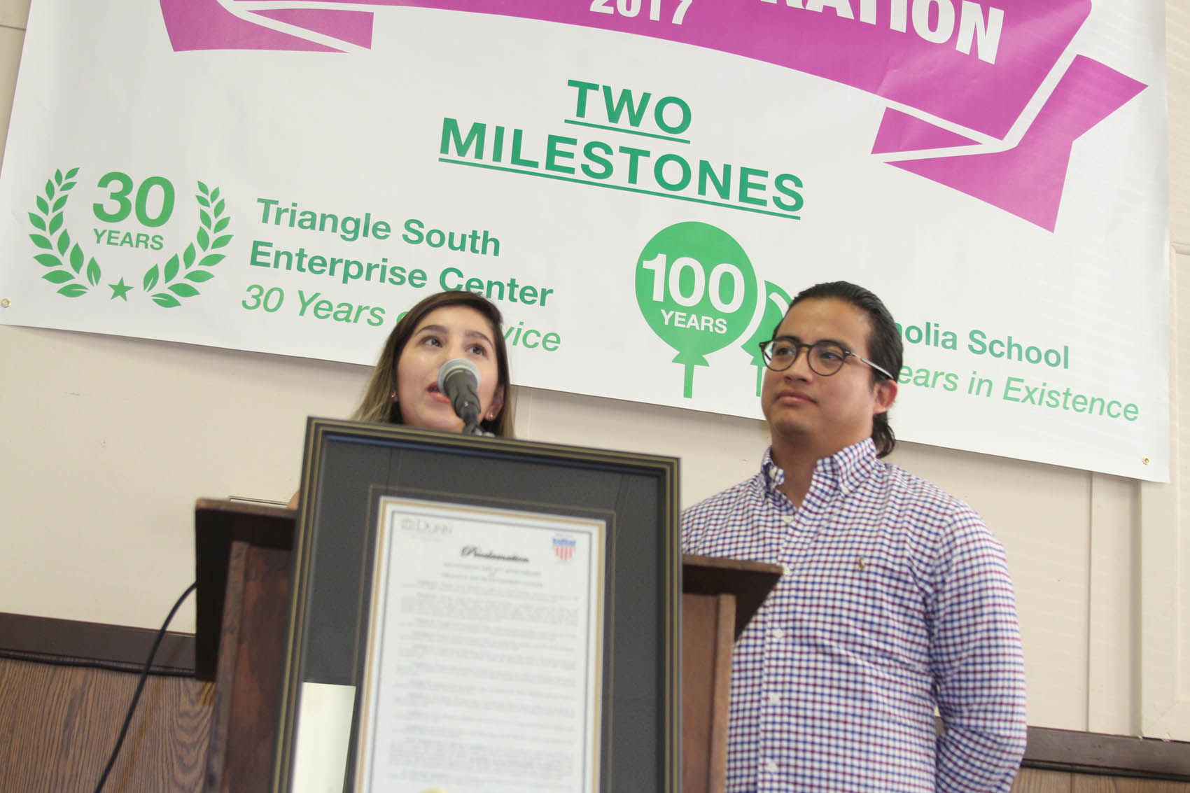 Click to enlarge,  Veronica Hernandez speaks during the celebration of Triangle South as her husband, Raul Hernandez, looks on. The couple started their business, Print-A-Tee, in the incubator program at Triangle South and graduated last month. Daily Record Photo by Melody Brown-Peyton.