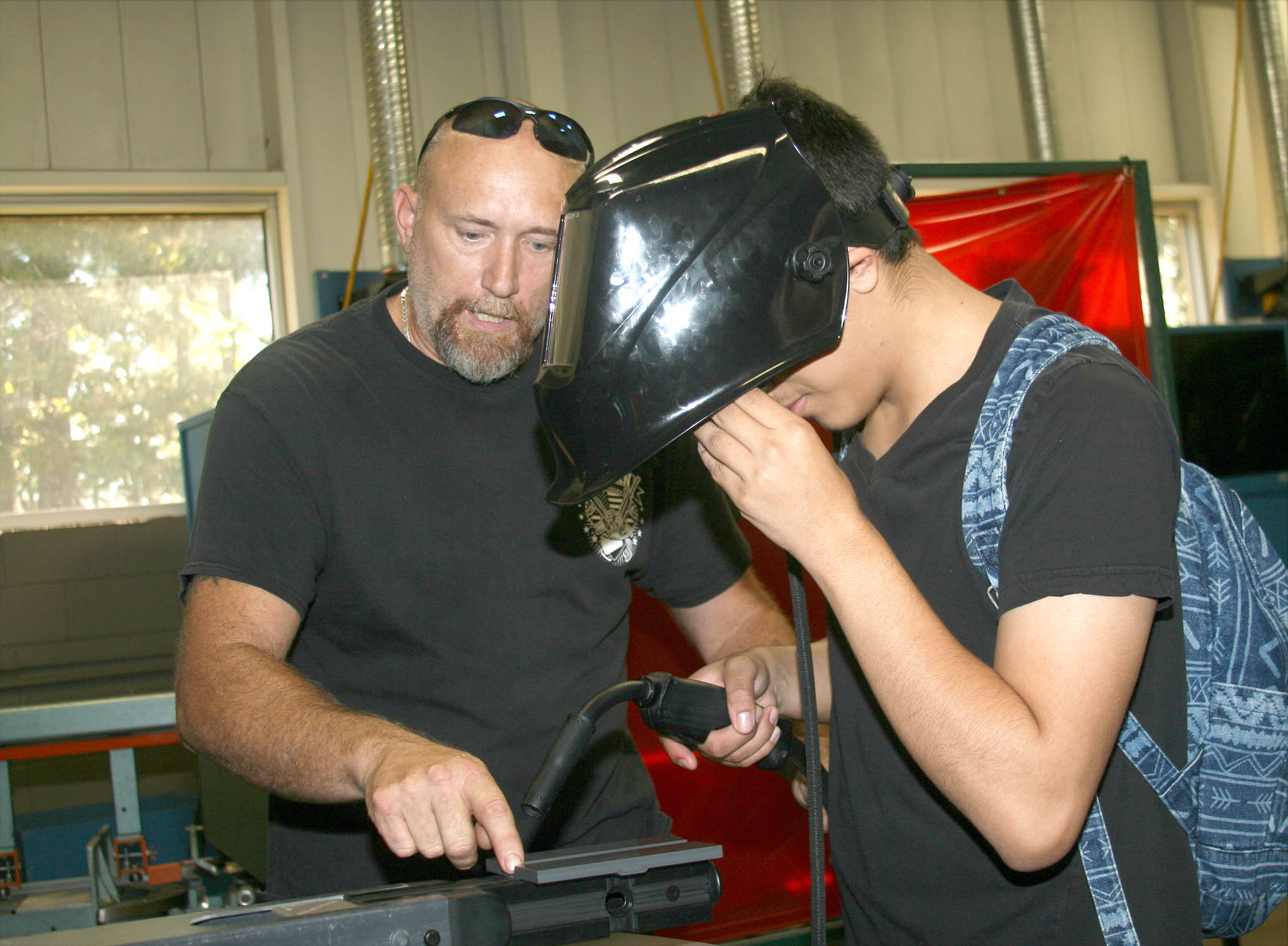 Click to enlarge,  Bryan Reyes (right) works at a welding simulator while Central Carolina Community College welding student Danny Collins watches during National Manufacturing Day at CCCC's Dr. Paul Howard and Dr. Barbara James Innovation Center.