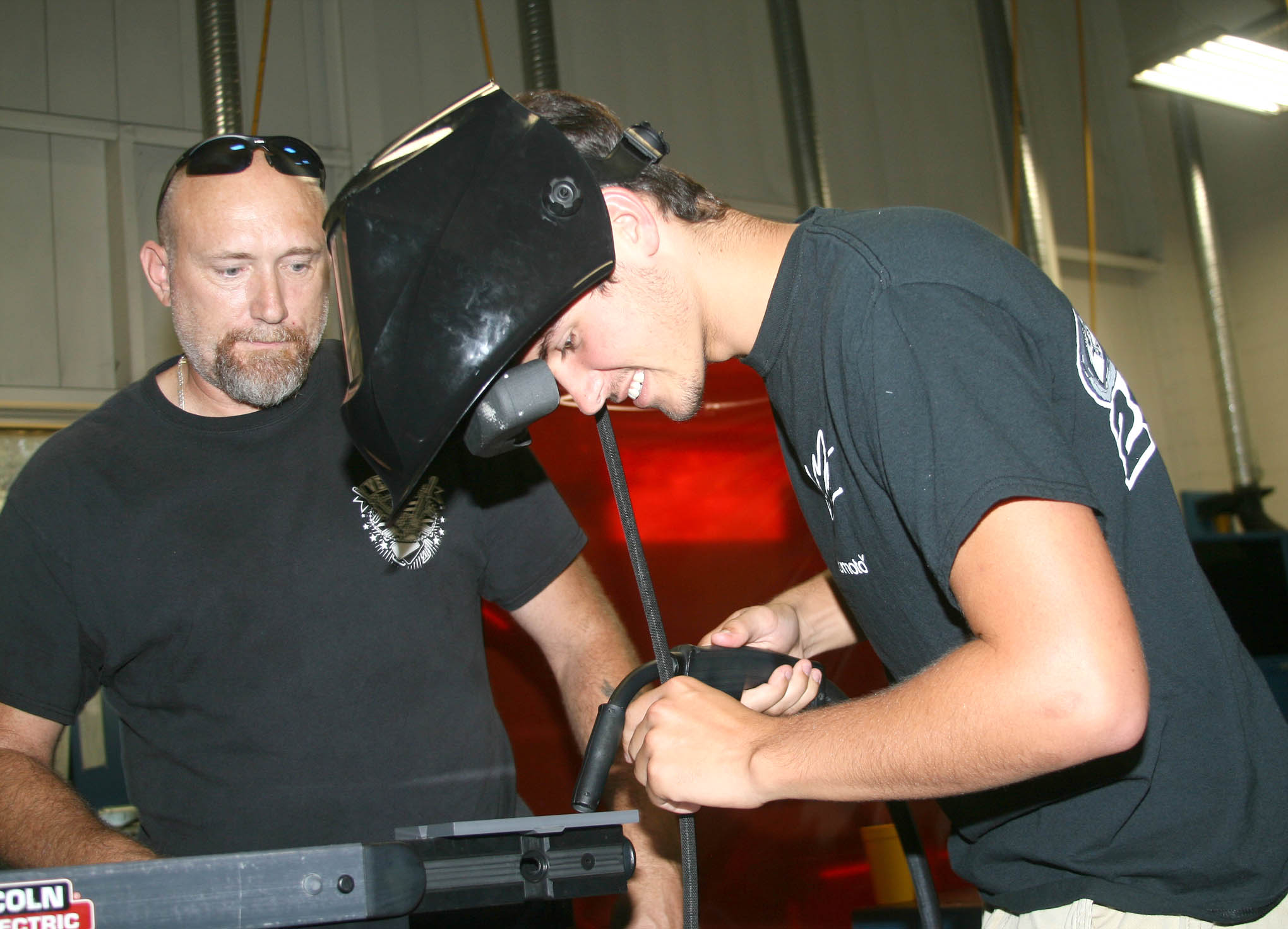 Click to enlarge,  J.C. Dooley (right) works at a welding simulator while Central Carolina Community College welding student Danny Collins watches during National Manufacturing Day at CCCC's Dr. Paul Howard and Dr. Barbara James Innovation Center.