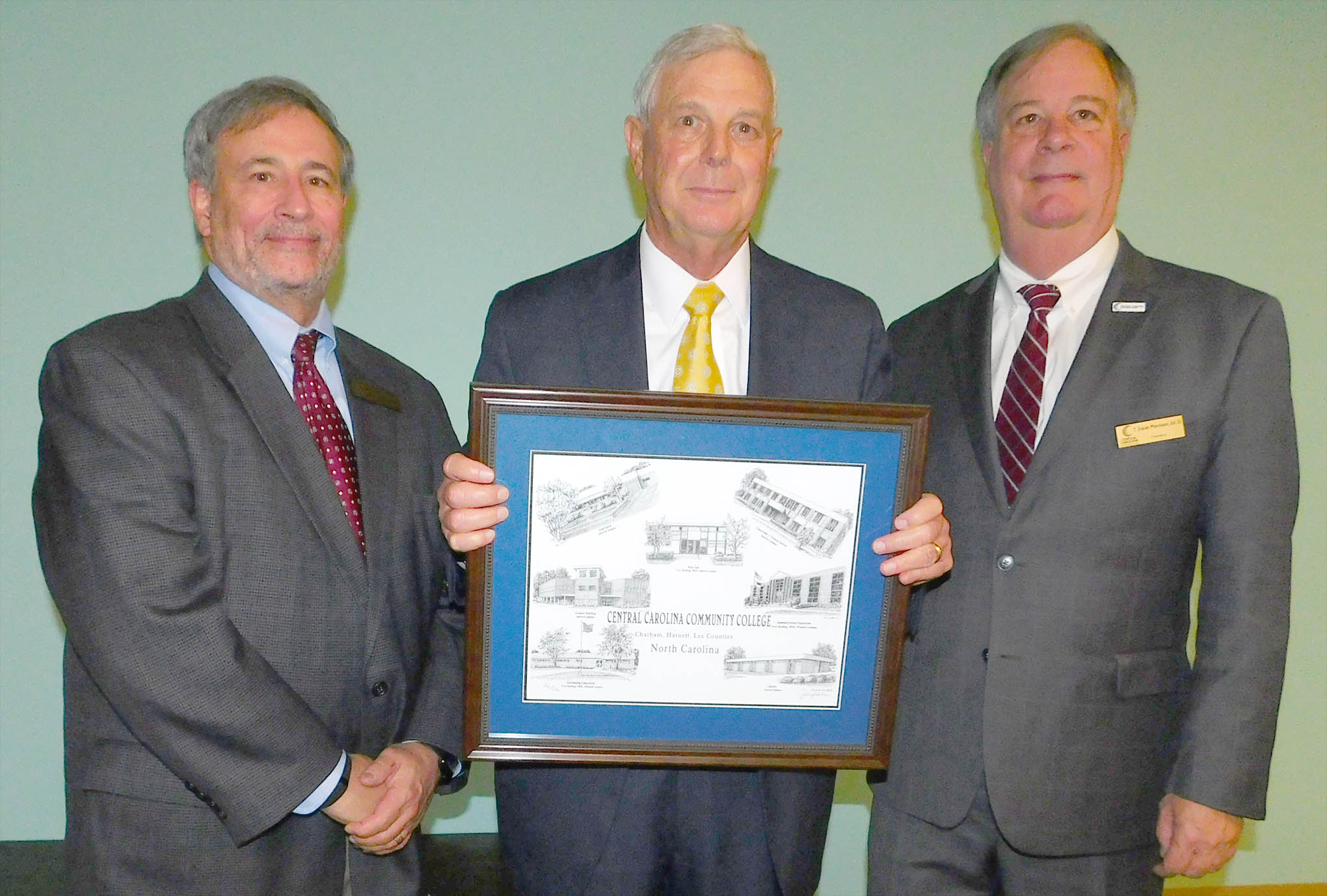 Click to enlarge,  Clem Medley (center), pictured with CCCC Board of Trustees Chairman Julian Philpott (left) and CCCC President T. Eston Marchant (right), was presented with a Jerry Miller print of CCCC buildings, as he was honored for his service as a CCCC Trustee on Wednesday, Nov. 1.