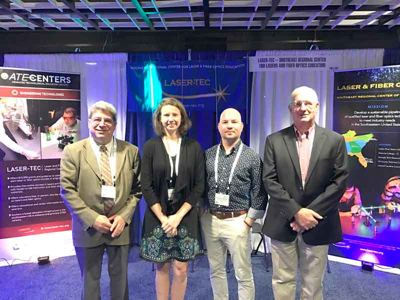 Click to enlarge,  Central Carolina Community College students Isabelle Karis (second from left) and Nickolas Jorgenson (second from right) are pictured at the CCCC student booth at the recent National Advanced Technological Education (ATE) Principal Investigators Conference in Washington, D.C. They are pictured with Dr. Chrys Panayiotou (left), of Indian Rivers State College, who is the Principal Investigator of the LASER-TEC NSF ATE Grant. At right is Gary Beasley, CCCC's Lead Laser Instructor.