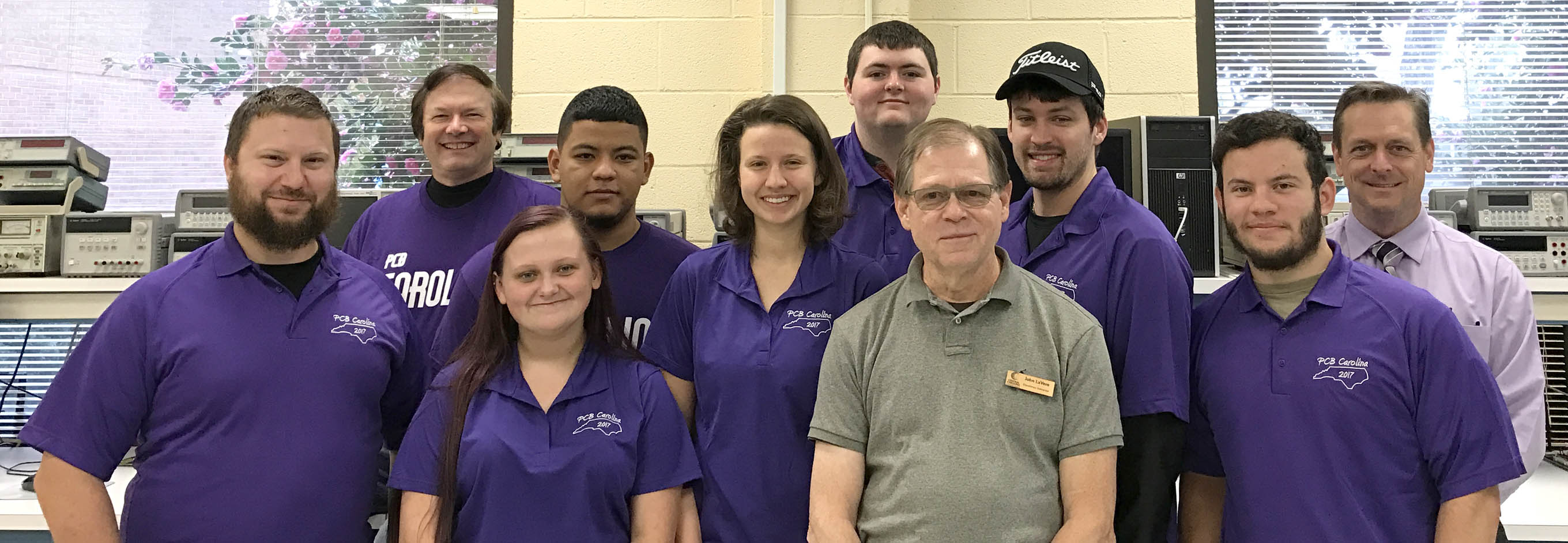 Click to enlarge,  Nine first-year students in the Central Carolina Community College Laser and Photonics Technology program served as volunteers with the PCB Carolina 2017 Electronics Trade Show and Technical Conference. Pictured are, left to right: Matthew Zannini, Robert Strickland, Brittany Cheek, Kilvet Zalavarria, Isabelle Karis, Ian Washburn, John LaVere (CCCC Harnett Electronics Instructor), Brandon Huffman, Cameron Wiedholz, and Dr. Jon Matthews (CCCC Harnett Provost). Volunteer not pictured is Jamie Turner.