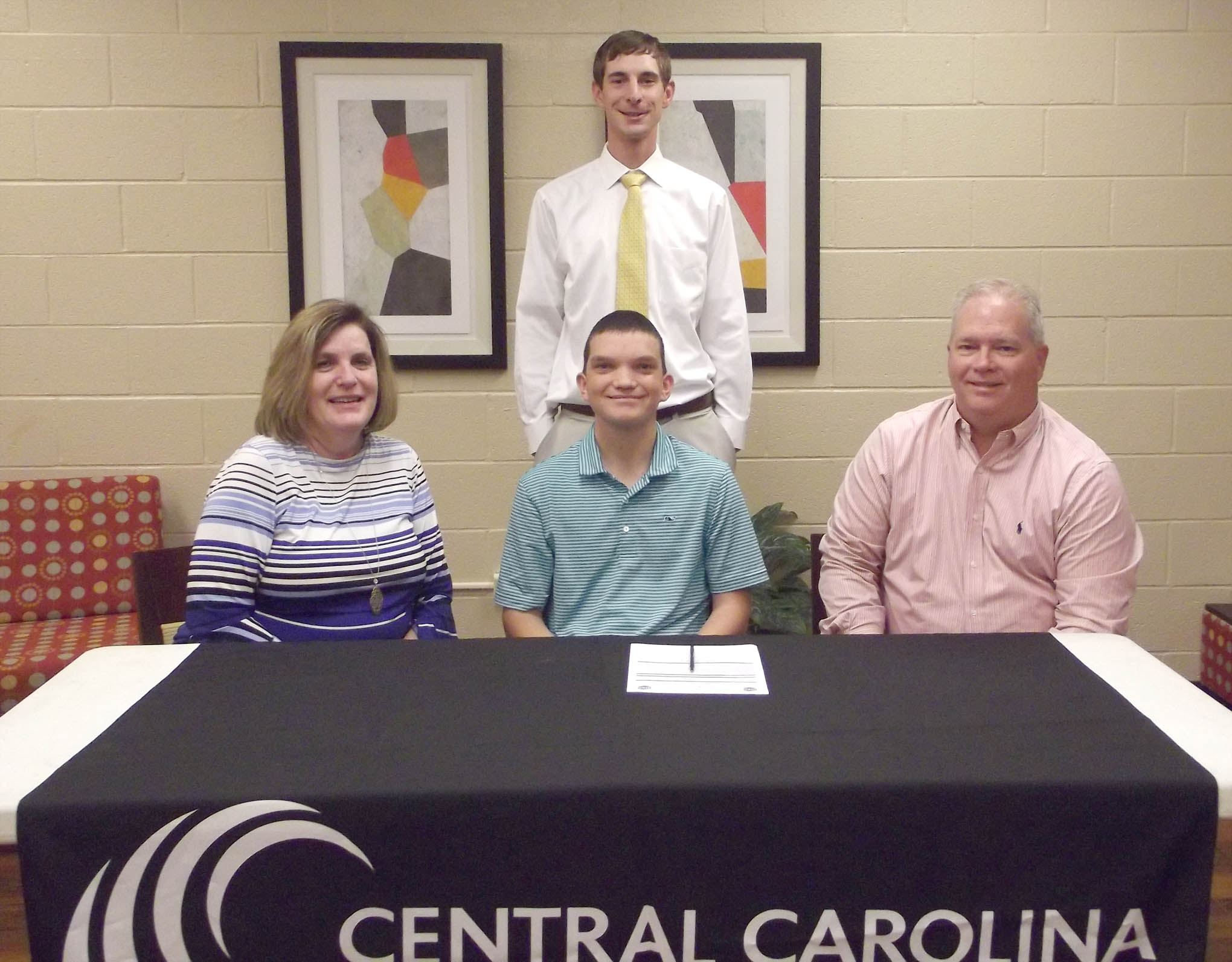 "Click to enlarge,  Justin Minter (seated, center) has signed to join next year's Central Carolina Community College men's golf team. He has played golf for four years at Southern Lee High School in Sanford. ""Justin is a great addition to our program,"" said CCCC Golf Coach Jonathan Hockaday (standing). Justin is pictured with his parents, Lisa and Ronald Minter."