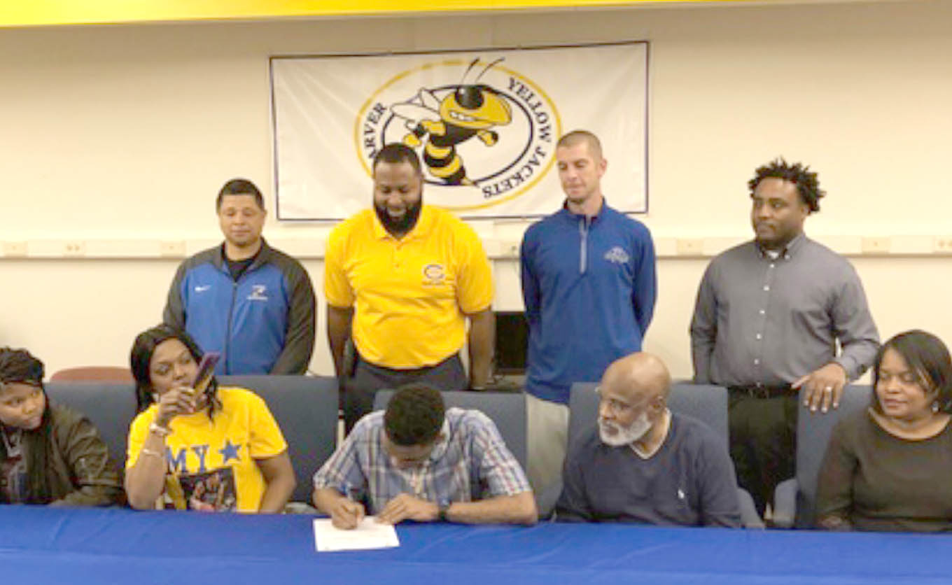 Click to enlarge,  Russell Bradley (seated, front), of Carver High School, signs with the Central Carolina Community College men's basketball program.