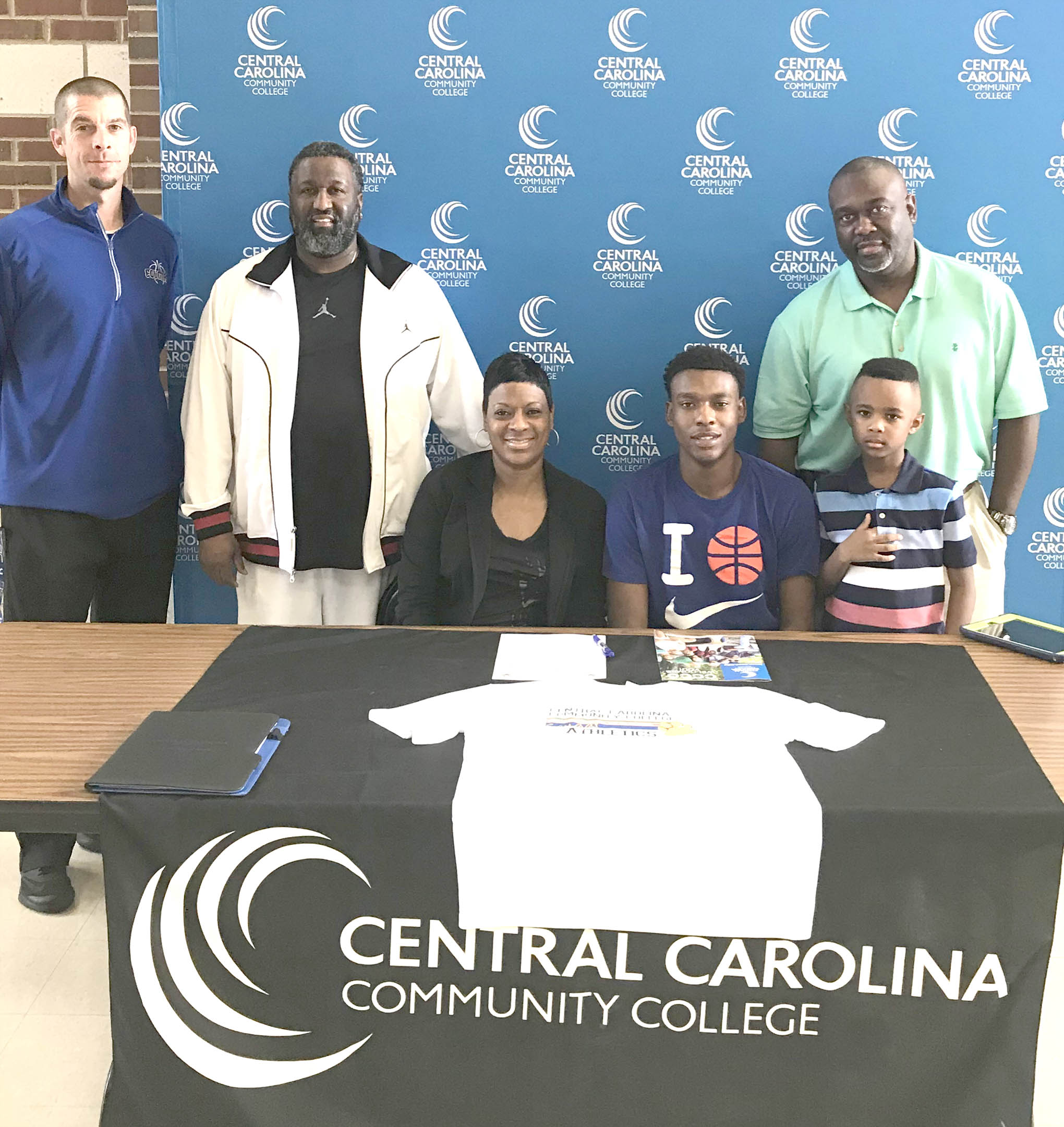 Click to enlarge,  Rodney Alston Jr., of Rocky Mount High School, signs with the Central Carolina Community College men's basketball program. Pictured with Alston and CCCC men's basketball coach Brad McDougald (left) are family members Marvin Hines, Cassandra Hines, Rodney Alston Jr., Dietrick Alston, and Rodney Alston.