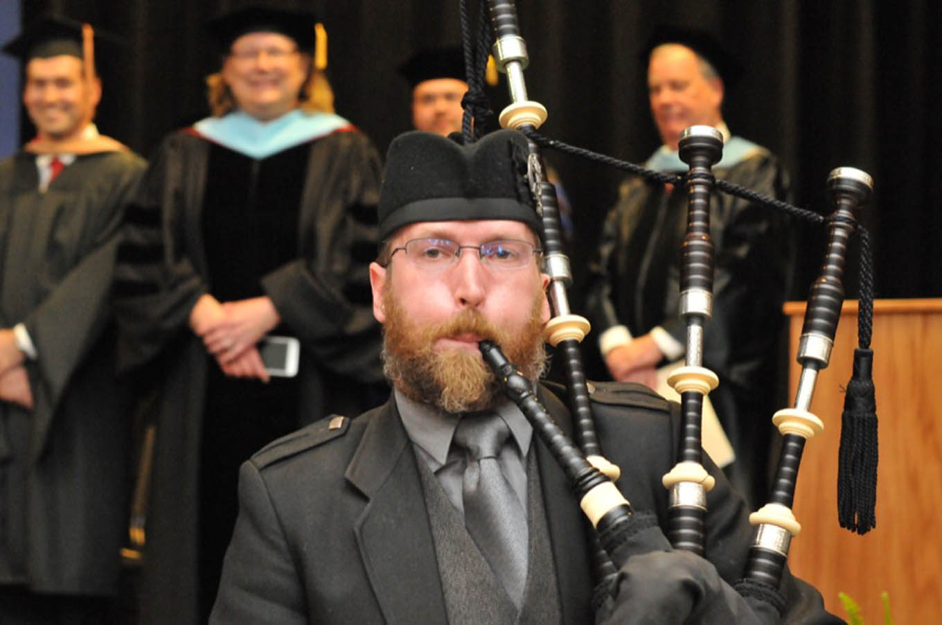Click to enlarge,  The Central Carolina Community College graduating students entered the main hall to the skirl of a bagpipe, a CCCC tradition.