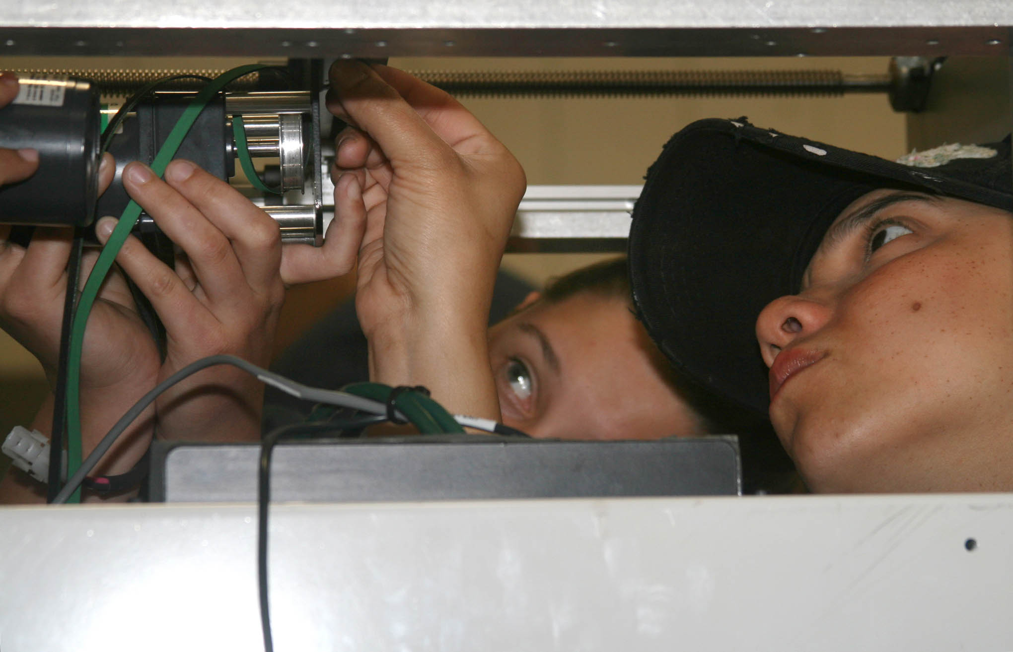 Click to enlarge,  Recently hired machine builders Claudia Maddox, left, and Yesenia Alicea get close to the equipment while installing electronics in an automated machine during an innovative training course developed by Central Carolina Community College and Conveyor Tech.