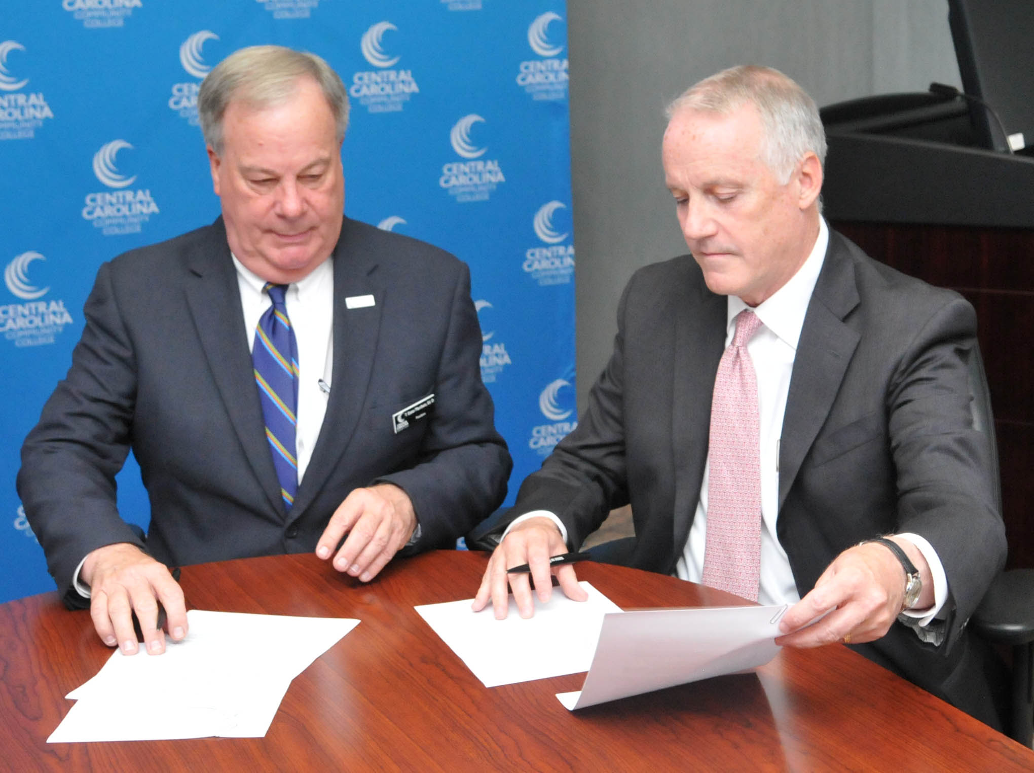 Click to enlarge,  Central Carolina Community College President Dr. T. Eston Marchant (left) and Dr. Louis D. Hunt, Senior Vice Provost for Enrollment Management at NC State University, sign a Memorandum of Understanding that promotes both associate degree and baccalaureate degree completion by giving guaranteed admission to N.C. State for CCCC students who meet the conditions of the program.