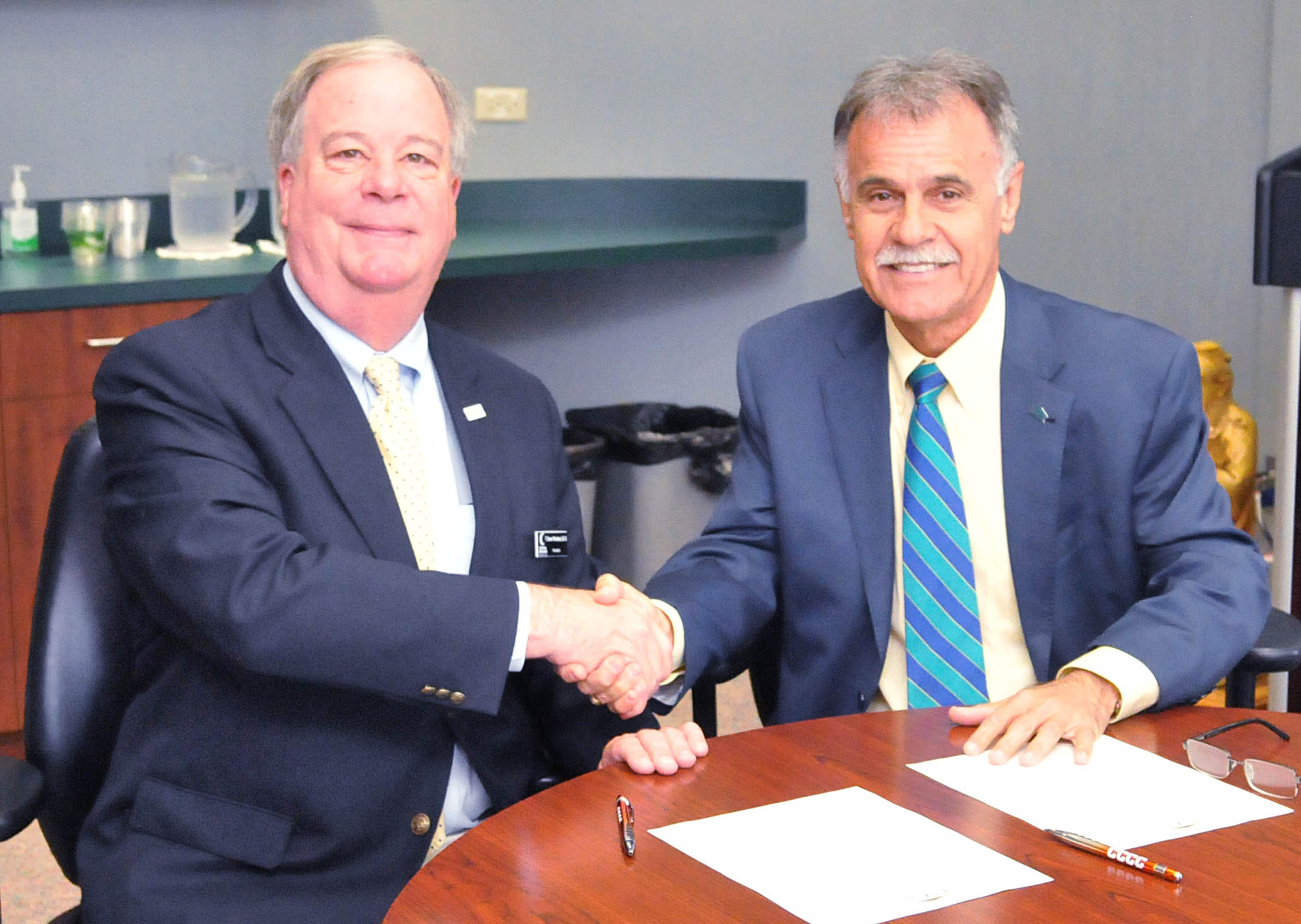 Click to enlarge,  Central Carolina Community College and The University of North Carolina Wilmington have agreed to a partnership called the Pathway to Excellence Program.  CCCC President Dr. T. Eston Marchant (left) and UNCW Chancellor Jose V. Sartarelli shake hands after signing the agreement.