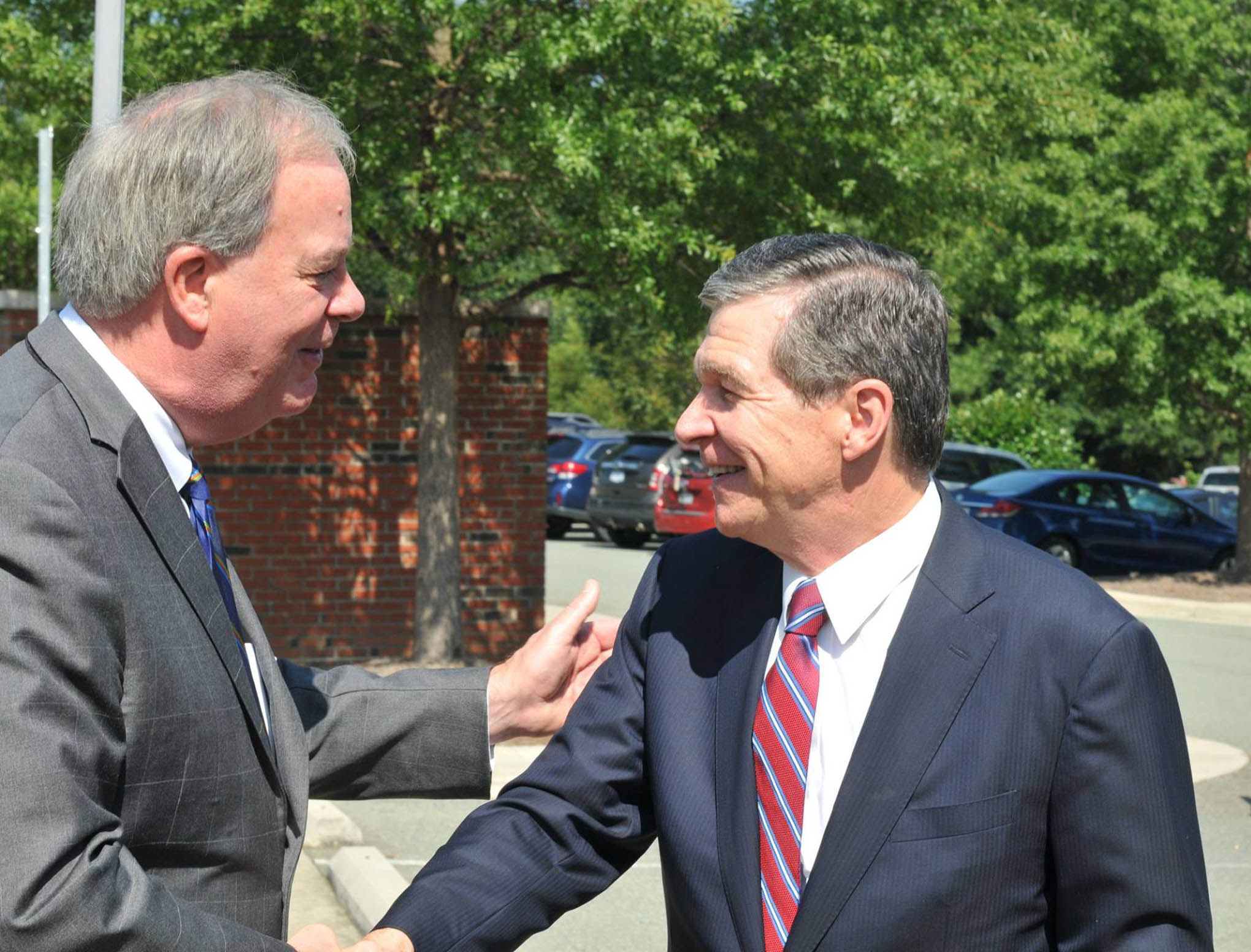 Click to enlarge,  Central Carolina Community College President Dr. T. Eston Marchant (left) greets N.C. Gov. Roy Cooper as he arrived at the CCCC Chatham Main Campus in Pittsboro on Thursday, Aug. 23.