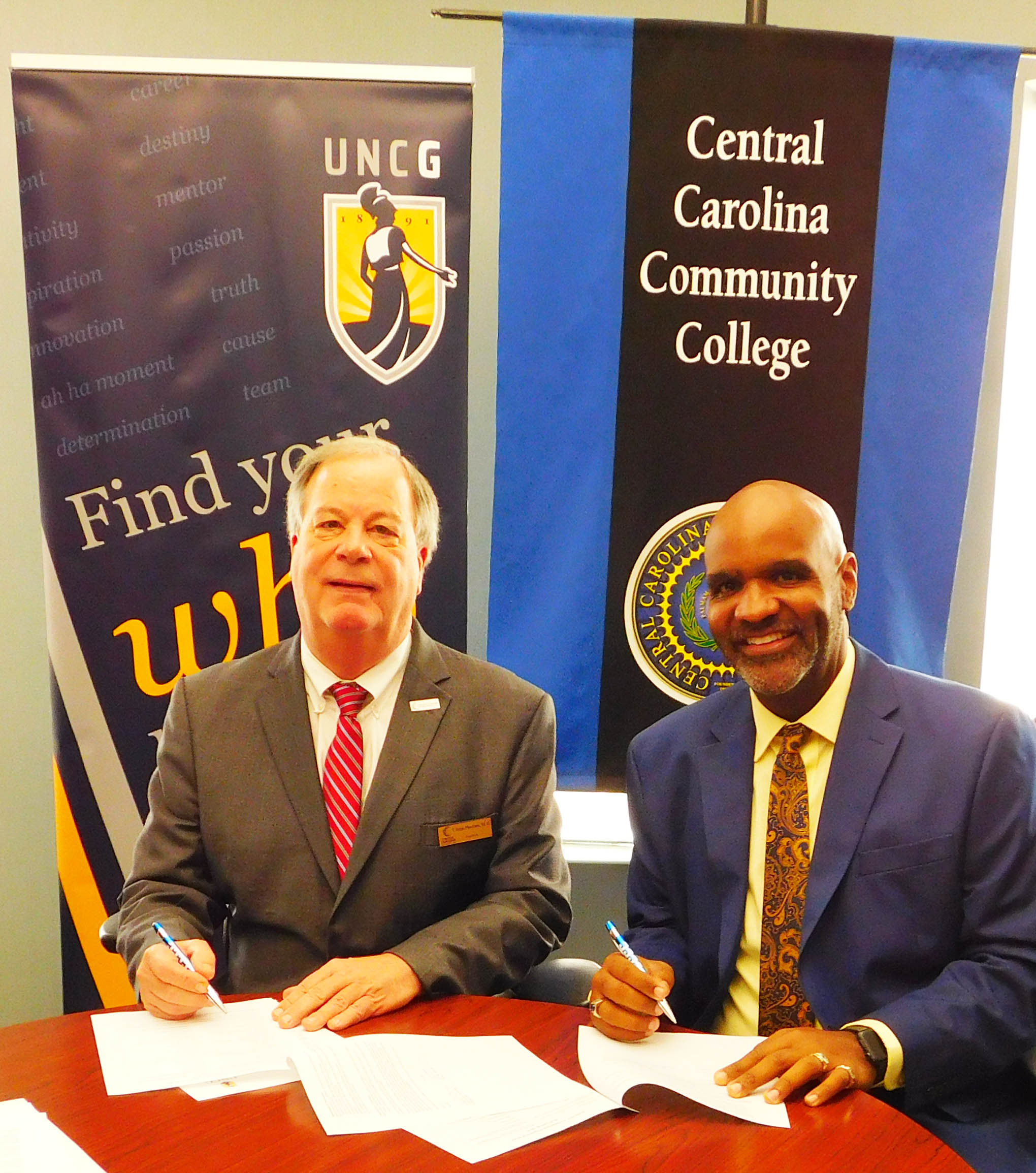 Click to enlarge,  Central Carolina Community College and The University of North Carolina at Greensboro have agreed to a new co-admission program called CCCC Spartan Passage. Signing the agreement are Dr. T. Eston Marchant (left), CCCC President, and Dr. Bryan Terry (right), UNCG Vice Chancellor for Enrollment Management.