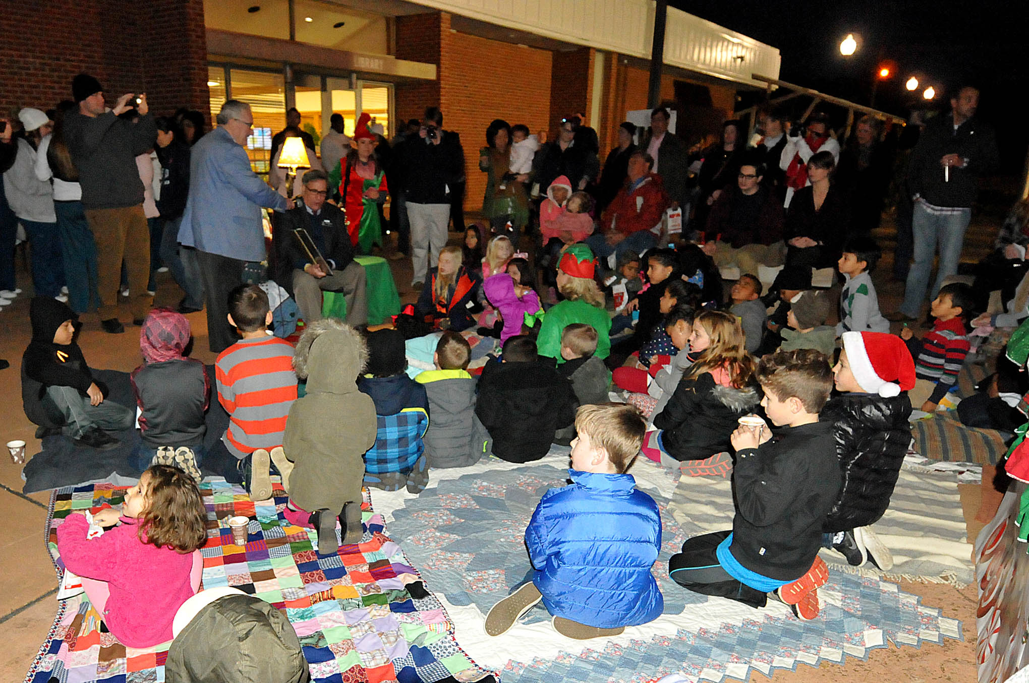 "Click to enlarge,  Children gathered around Julian Philpott, Central Carolina Community College Board of Trustees Chairman, listening eagerly as he read Clement Moore's holiday classic, ""'Twas the Night Before Christmas,"" at the CCCC Foundation Christmas Tree Lighting celebration."