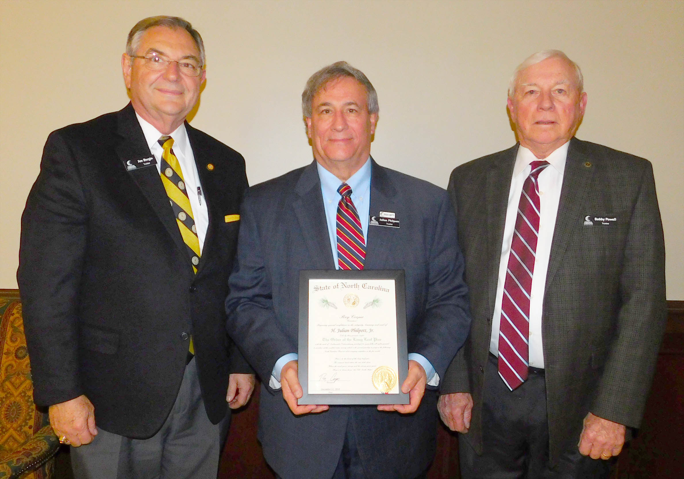 "Click to enlarge,  H. Julian Philpott Jr. (center), Chairman of the Central Carolina Community College Board of Trustees, recently received The Order of the Long Leaf Pine, a prestigious award given by the Governor of North Carolina. Philpott is a corporate attorney who has spent the last 30 years working as a lobbyist and general counsel for the nonprofit North Carolina Farm Bureau Federation and its affiliated companies. He is now a Senior Partner with Hayes Group Consulting. Pictured with Philpott are two other members of the CCCC Board of Trustees who also have received The Order of the Long Leaf Pine -- State Sen. Jim Burgin (left) and L.W. ""Bobby"" Powell (right)."