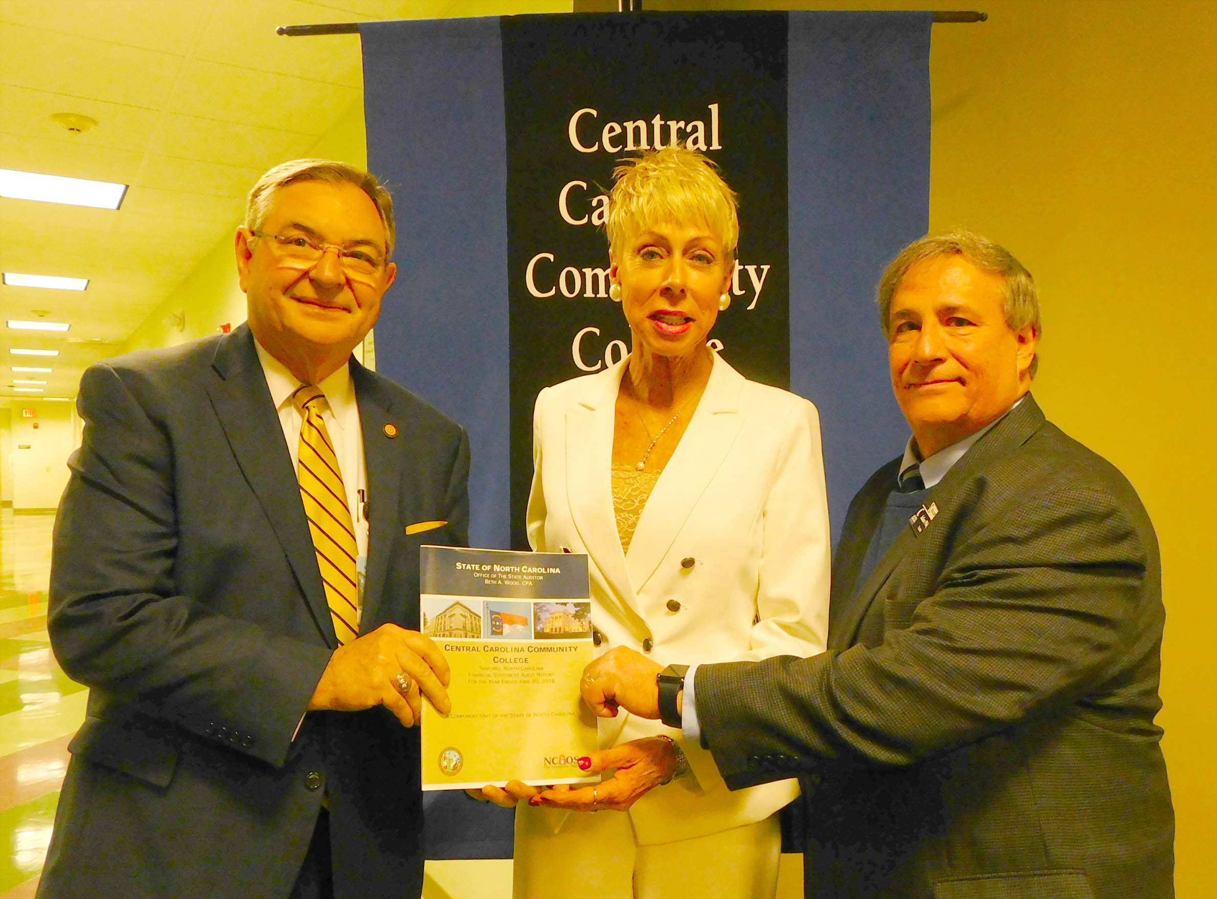 Click to enlarge,  North Carolina State Auditor Beth A. Wood (center) visits with CCCC Trustees Vice Chairman Jim Burgin (left) and Chairman Julian Philpott (right).