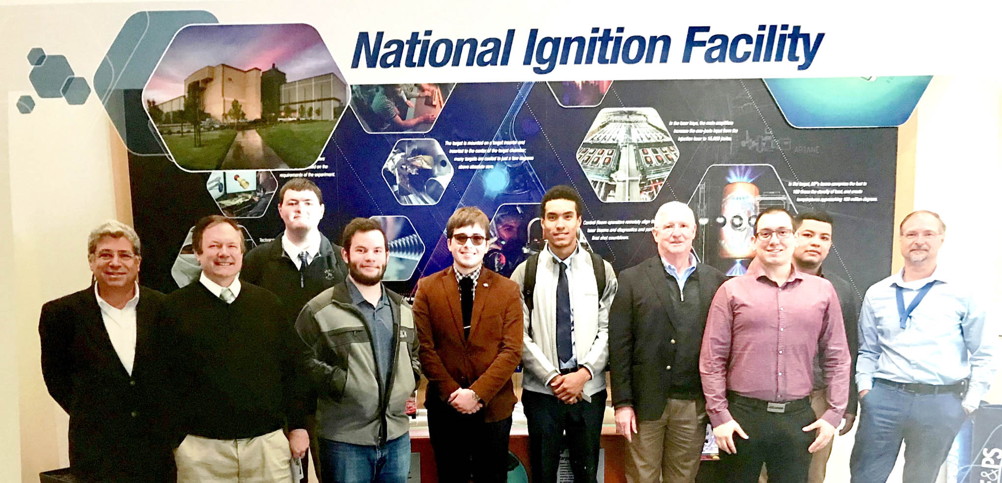 Click to enlarge,  Second-year students in the Laser and Photonics Technology program at Central Carolina Community College's Harnett Main Campus toured the LLNL NIF Facility in California. Pictured are, left to right: Chrysanthos Panayiotou (LASER-TEC Principal Investigator), Robert Strickland, Ian Washburn, Cameron Wiedholz, Jamie Turner, Brandon Pasley, Gary Beasley (lead instructor), Al Delong (2015 CCCC Laser Graduate with LLNL, who help lead the tour), Kilvet Zalavarria, and Brian Olejniczak (LLNL Laser Systems Engineering & Operations Director).