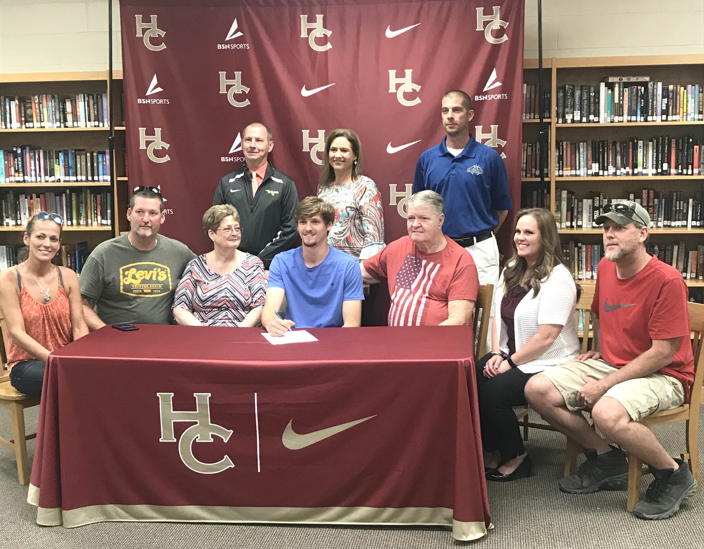 Click to enlarge,  Chase Mullins (seated, center), of Harnett Central High School, signs with the Central Carolina Community College men's basketball program.