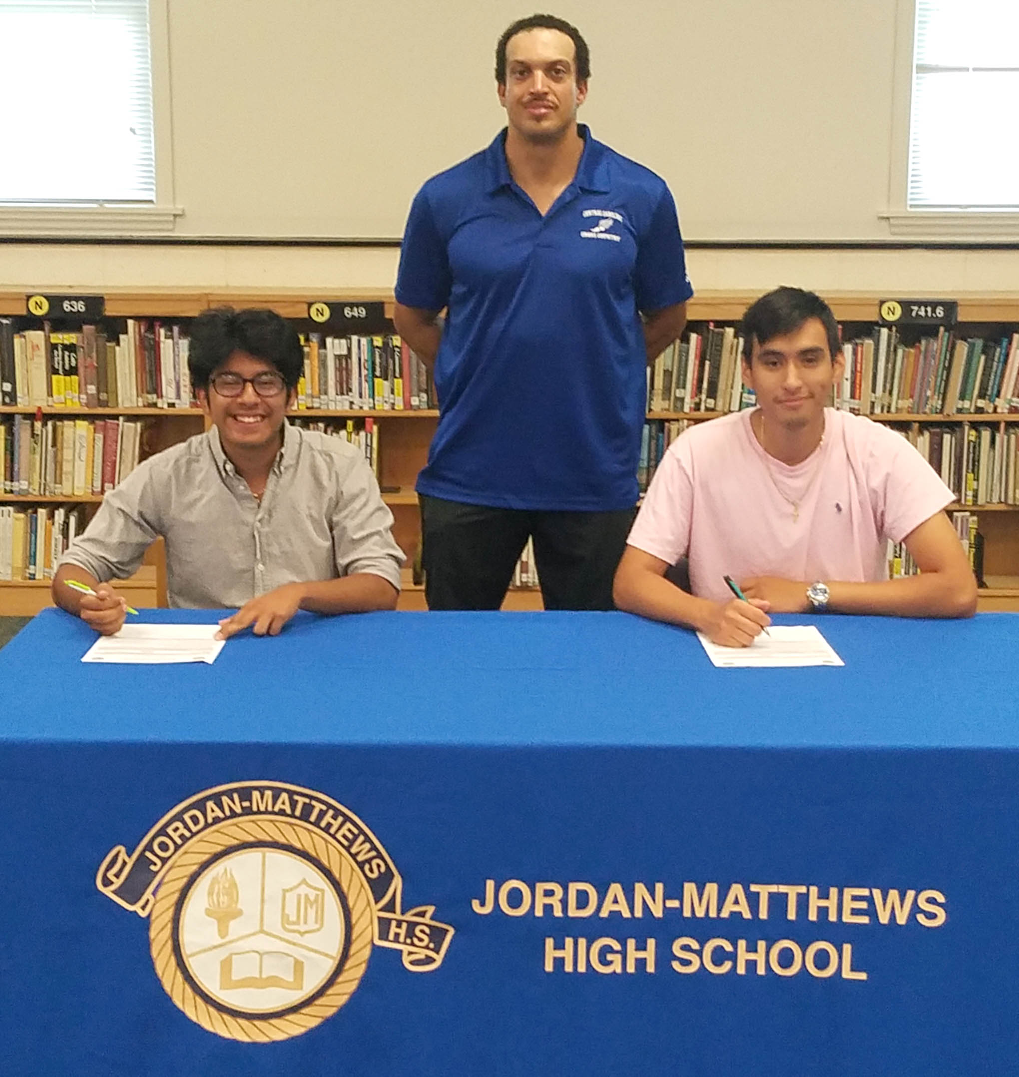 Click to enlarge,  Eddy Girron (seated, left) and George Jucinto (seated, right) sign with the Central Carolina Community College cross country program. Standing is CCCC Head Cross Country Coach Richard Briggs.