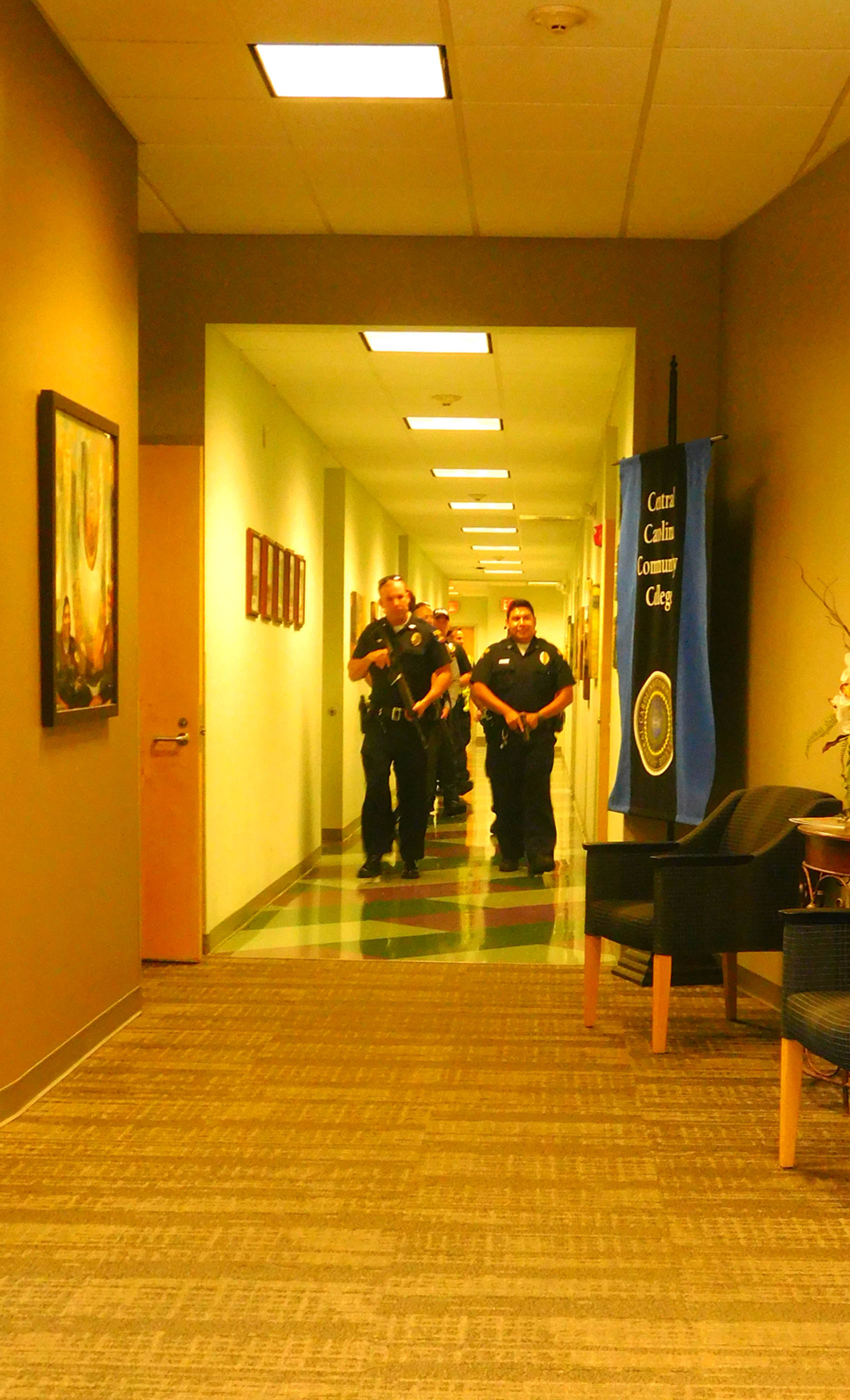 Click to enlarge,  Law enforcement officers walk down a hallway during a recent active assailant drill on the Central Carolina Community College Lee Main Campus.
