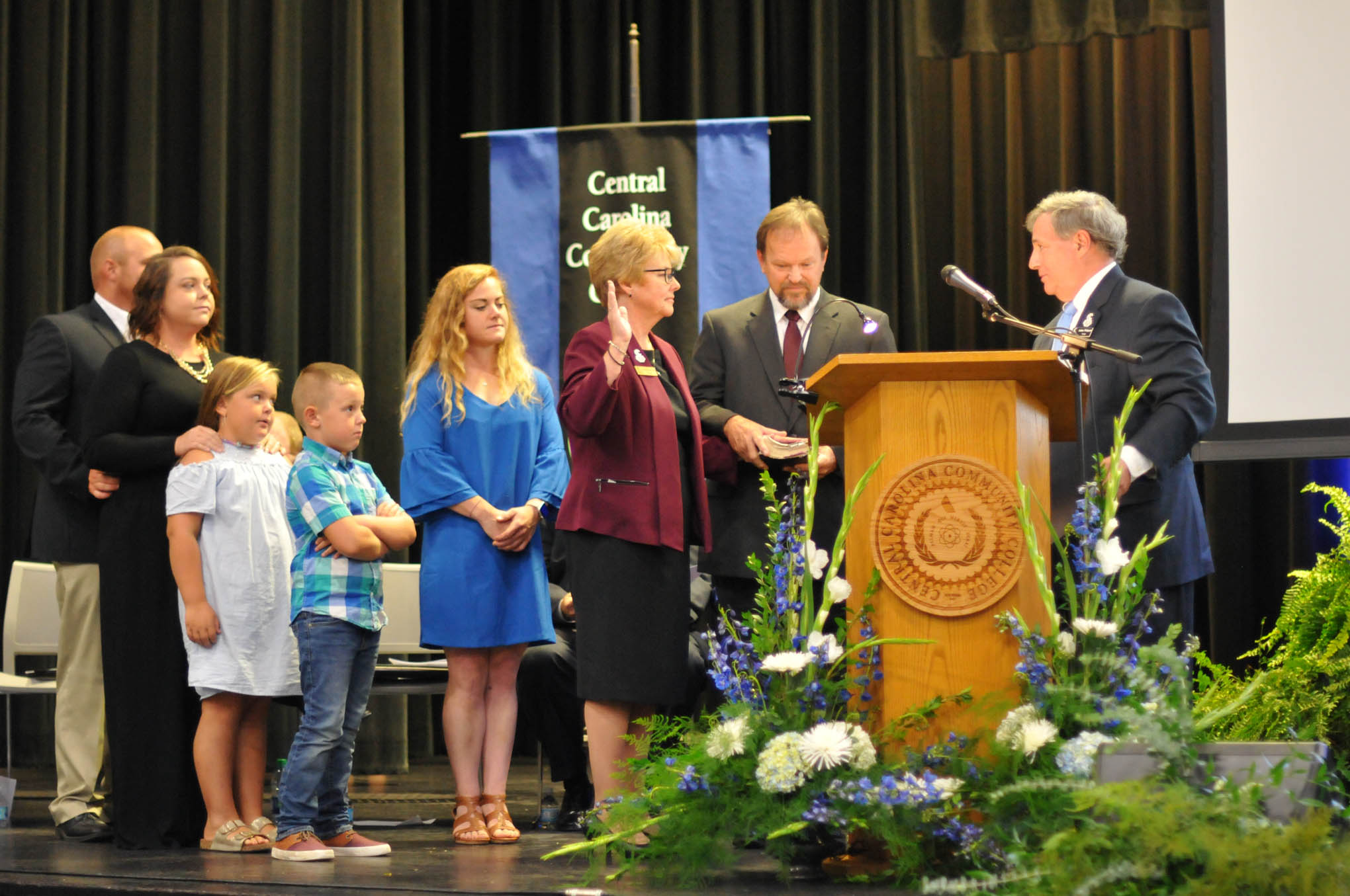 Click to enlarge,  Central Carolina Community College President Dr. Lisa M. Chapman receives the Oath of Office from Julian Philpott, Chairman of the CCCC Board of Trustees, as Dr. Chapman's family joins her on stage for her Installation as CCCC President on Sept. 26.