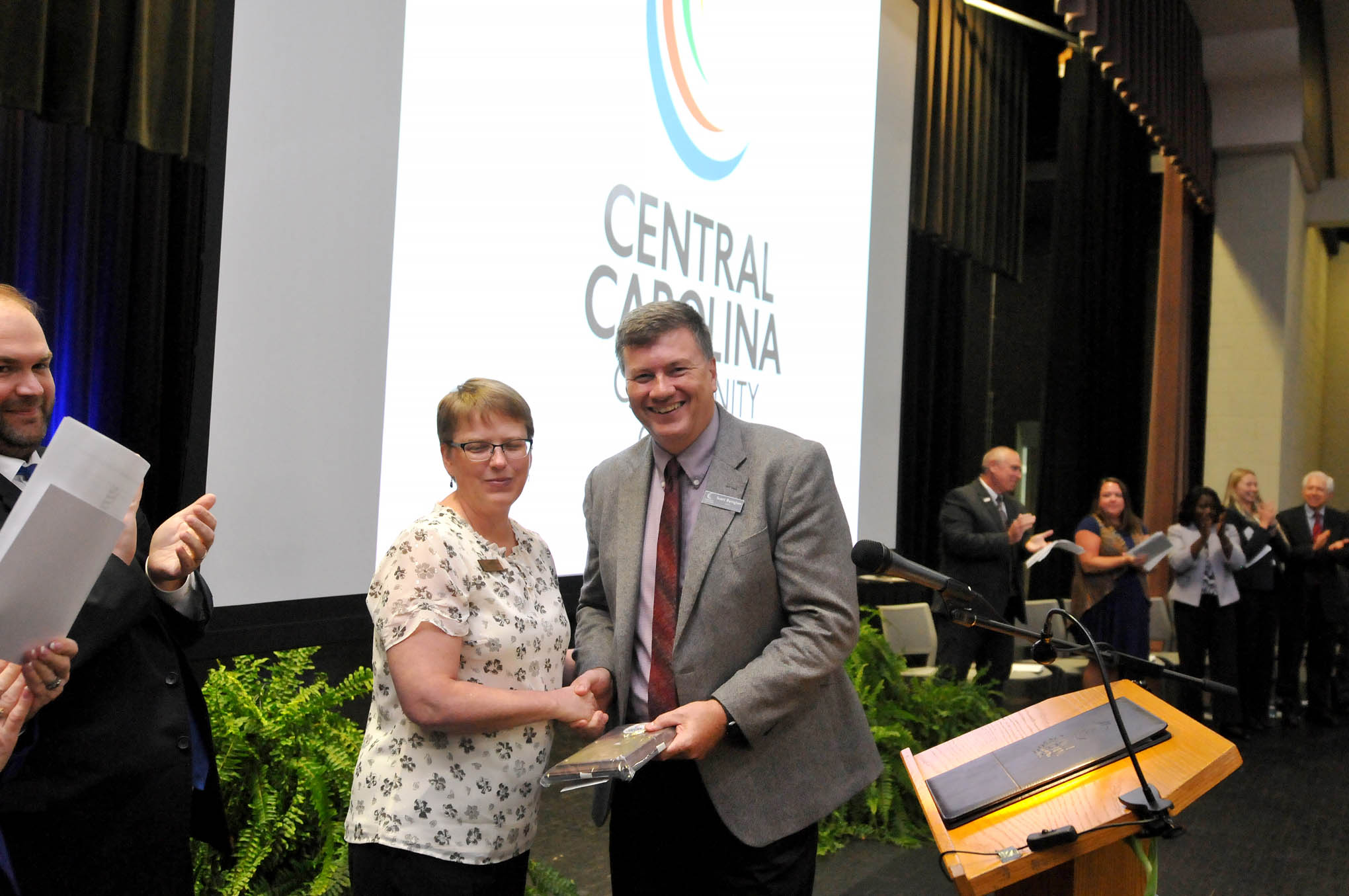 Click to enlarge,  Central Carolina Community College Dean of Arts, Sciences and Advising Scott Byington (right) receives the Staff Member of the Year award from 2018 recipient and CCCC Student Learning Coordinator Angela Crisp-Sears (left) during the Convocation and Installation of Dr. Lisa M. Chapman as Sixth President of CCCC on Sept. 26.