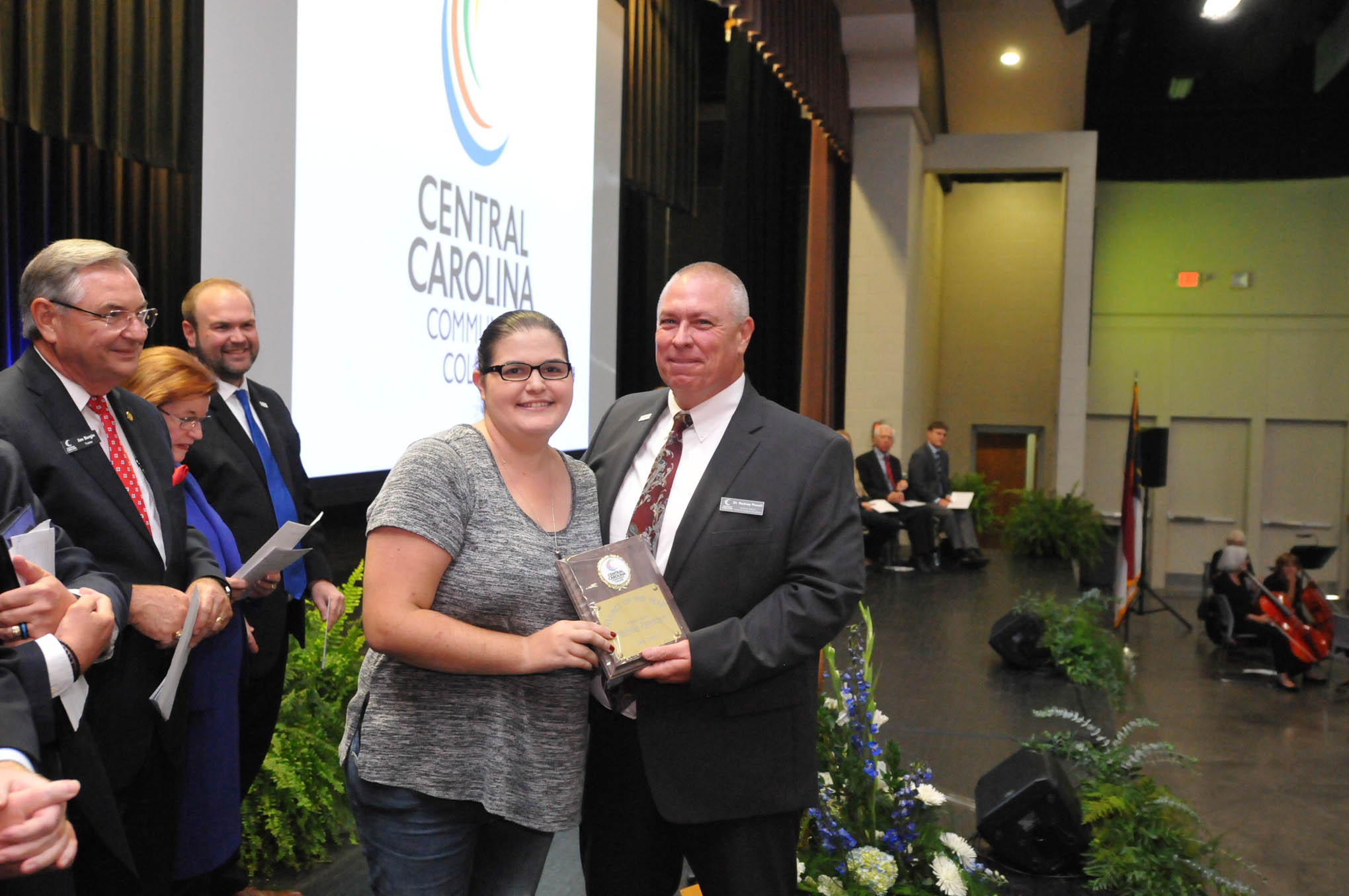 Click to enlarge,  Michelle Patterson (left), a Central Carolina Community College Veterinary Medical Technology Instructor, receives the Adjunct of the Year award from Dr. Rodney Powell (right), CCCC Executive Director of the Center for Academic Excellence, during the Convocation and Installation of Dr. Lisa M. Chapman as Sixth President of CCCC on Sept. 26.