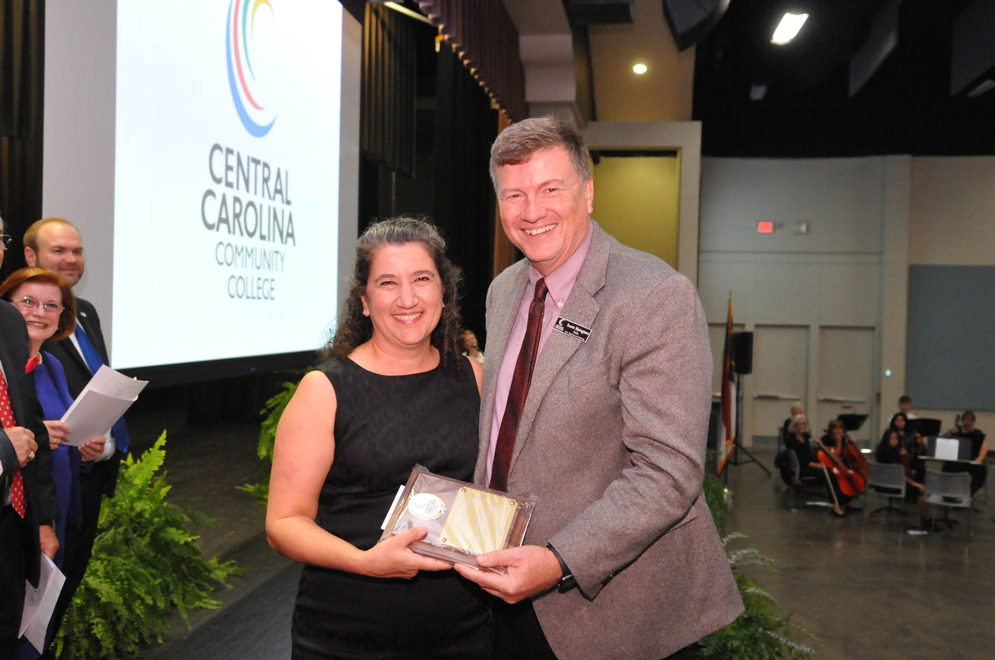 Click to enlarge,  Dr. Lora Witcher (left) receives the Central Carolina Community College Advisor of the Year award from Scott Byington (right), CCCC Dean of Arts, Sciences and Advising, during the Convocation and Installation of Dr. Lisa M. Chapman as Sixth President of CCCC on Sept. 26.