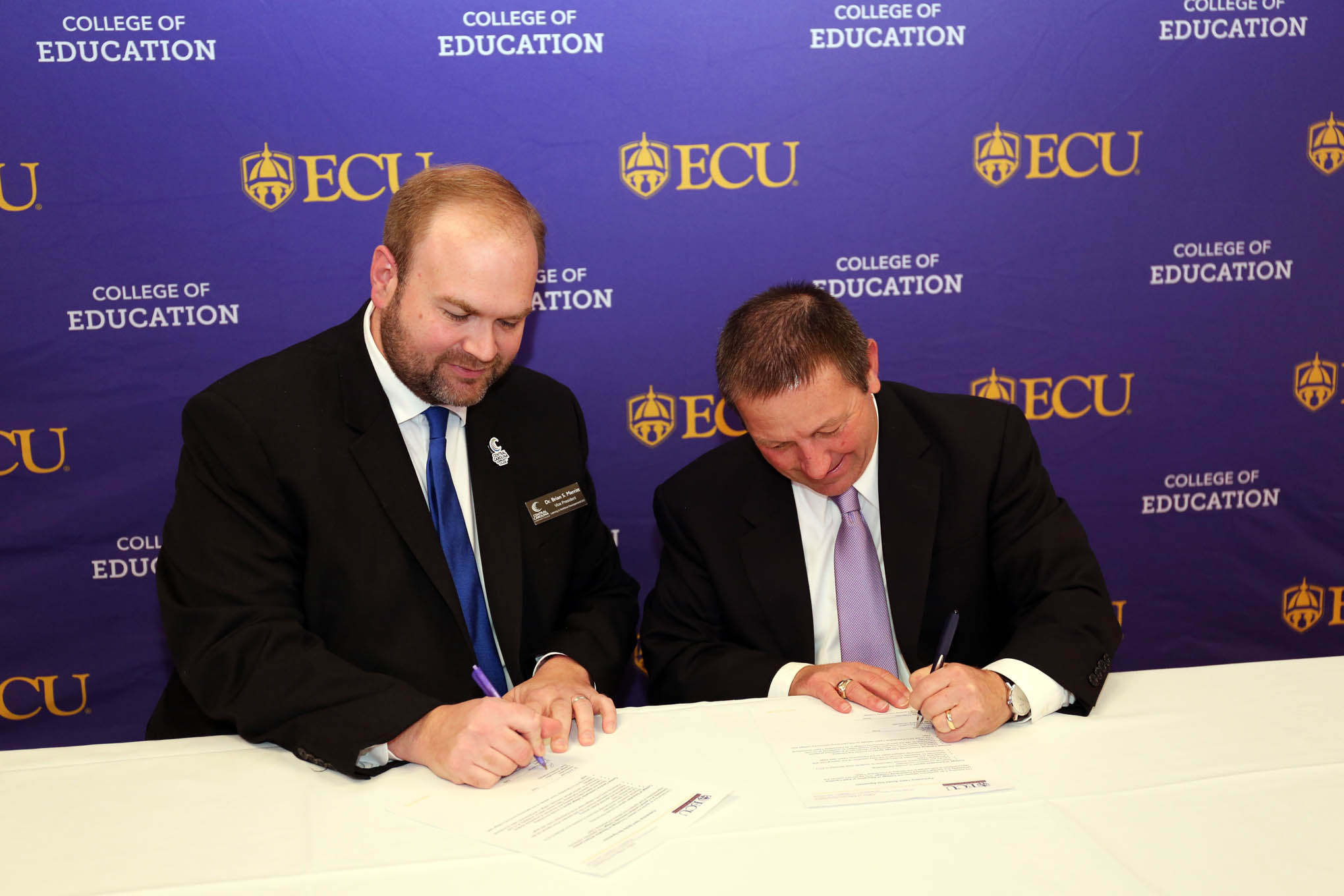 Click to enlarge,  Dr. Brian Merritt (left), Central Carolina Community College Vice President of Learning & Workforce Development/Chief Academic Officer, and Dr. Art Rouse, East Carolina University's Interim Dean of the College of Education, sign the Partnership Teacher program agreement.