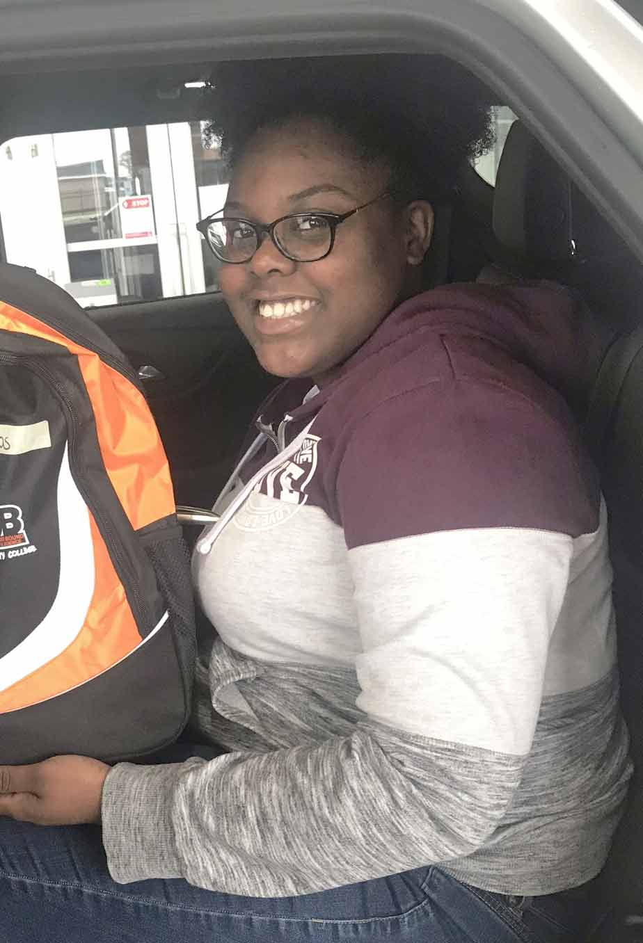 Click to enlarge,  Candice Douglass shows off the book bag she received that was filled with school supplies and STEM related items for hands-on learning activities for the TRIO Upward Bound summer program.